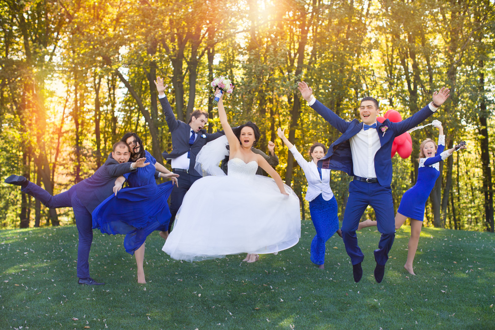 jumping for joy in their wedding photo